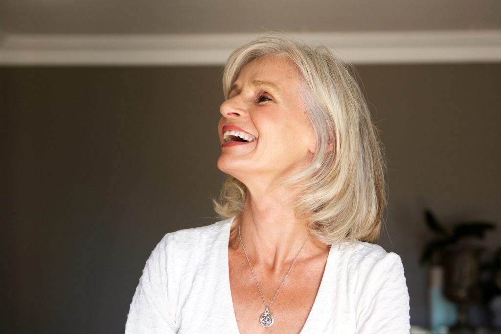 laughing older woman standing inside home